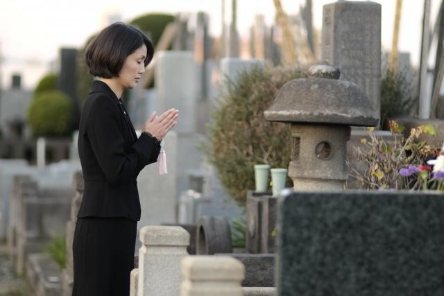 お墓に手を合わせる女性