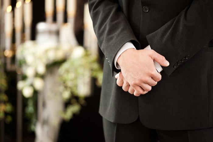 葬儀で手を組む男性